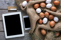 Fresh chicken eggs on sack and tablet, internet order concept Stock Photo