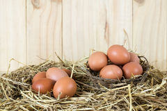 Fresh chicken eggs in the straw nest on wooden vintage backgroun Royalty Free Stock Photo