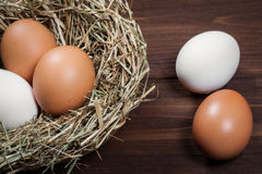 Fresh chicken eggs on a wooden table. Nest with white and brown eggs Royalty Free Stock Image