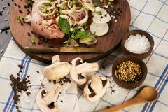 Fresh chicken fillet with fresh vegetables mushrooms. Onion rosemary and seasoning spices on dark wooden board. Culinary cooking ingredients. Healthy diet food Stock Images