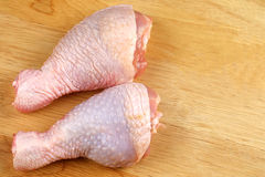Fresh chicken legs on a cutting board - close up Royalty Free Stock Images