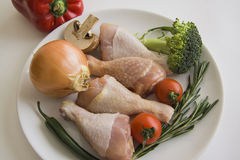 Fresh chicken legs with vegetables. Chicken legs with summer vegetables Royalty Free Stock Image