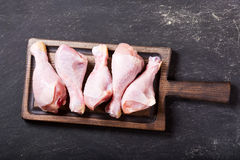Fresh chicken legs on wooden board. Top view Royalty Free Stock Photo