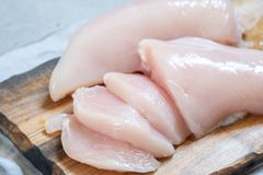 Fresh chicken meat on wooden board. Fresh raw chicken breast meat on wooden board Royalty Free Stock Photos