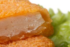 Fresh chicken nuggets cut into green lettuce close up Stock Images
