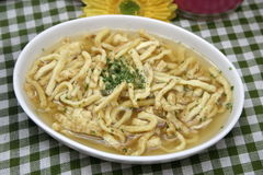 Chicken soup. A fresh chicken soup with some slices of a pancake royalty free stock image