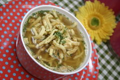 Chicken soup. A fresh chicken soup with some slices of a pancake Royalty Free Stock Photography