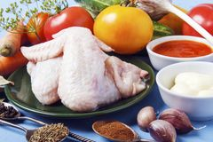 Fresh chicken wings for cooking diet dinner or dinner. Organic natural vegetables for garnish. Ingredients for healthy dish.  royalty free stock images