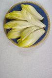 Fresh Chicory Salad leaves placed on a blue plate. On white background copy space Royalty Free Stock Images