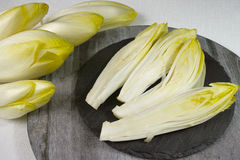 Fresh Chicory Salad leaves placed on a grey stone board. And wooden plate Royalty Free Stock Photo