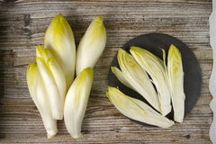 Fresh Chicory Salad leaves placed on a grey stone board. On wooden table Stock Photography