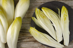 Fresh Chicory Salad leaves placed on a grey stone board. On wooden table Stock Images