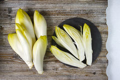 Fresh Chicory Salad leaves placed on a grey stone board. On wooden table Stock Photo