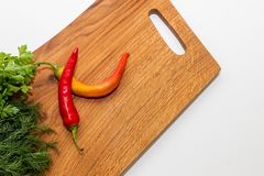 Fresh chili pepper, parsley and dill on board, closeup.wooden board with vegetables and condiments isolated on white. Fresh chili pepper, parsley and dill on stock images
