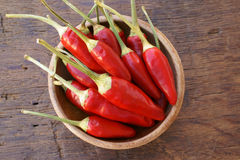 Fresh chili pepper pods. In a wooden bowl on a rustic wooden table with copy space Royalty Free Stock Image