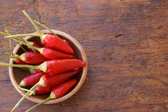 Fresh chili pepper pods. In a wooden bowl on a rustic wooden table with copy space Stock Image