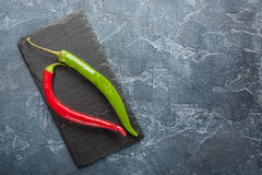 Fresh  chili peppers on a dark stone with expressive texture Stock Photo