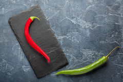 Fresh  chili peppers on a dark stone with expressive texture Royalty Free Stock Image