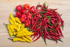 Mixed red and yellow hot chili peppers on a light wooden table stock photos