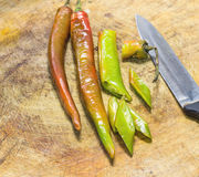 Fresh chillies being sliced with old chefs knife Stock Image