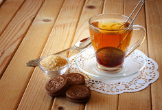 Fresh chocolate cookies and hot black tea over wooden table Royalty Free Stock Image