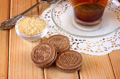 Fresh chocolate cookies and hot black tea over wooden table Stock Photo