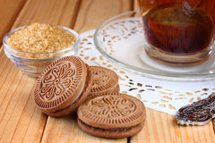 Fresh chocolate cookies and hot black tea over wooden table Stock Image