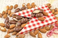 Fresh and chocolate covered almonds. Falling out of decorated box stock photo