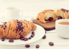 Fresh chocolate croissants and cup of coffee on white rustic woo Stock Photography