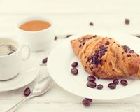 Fresh chocolate croissants and cup of coffee on white rustic woo Royalty Free Stock Photography