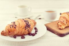 Fresh chocolate croissants and cup of coffee on white rustic woo Stock Images