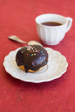 Fresh chocolate donut on a napkin with a cup of tea Royalty Free Stock Images