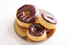 Fresh chocolate donuts. Freshly baked delicious chocolate donuts on a shiny plate. White background, not isolated stock photos