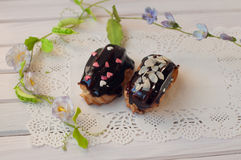 Fresh chocolate eclairs lay on white lace serviette with green stems and flowers Stock Images