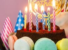 Fresh cholocate delicious cake with maracoons around it with topper Happy birthday and burning candles on the table