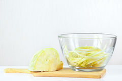Fresh chopped cabbage in a glass bowl on a cutting board Royalty Free Stock Photography