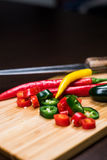 Fresh, chopped hot peppers on cutting board Royalty Free Stock Photos