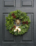 Fresh Christmas wreath on a door. Fresh Christmas holiday wreath on an old style English black wooden door with a gold lion head knocker Stock Image
