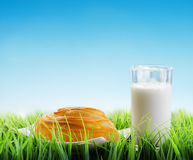 Fresh cinnamon bun and glass of milk on sky background Royalty Free Stock Image