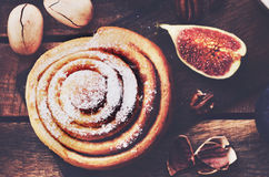 Fresh cinnamon bun with pecan nuts topped with sugar powder Royalty Free Stock Photography