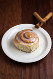 Fresh Cinnamon Roll. A fresh cinnamon roll on a plate with cinnamon sticks Royalty Free Stock Images