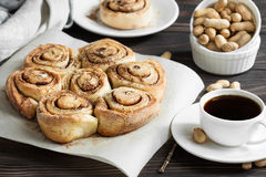 Fresh cinnamon rolls and coffee for southern breakfast table. Buns with cinnamon and nuts, espresso cup Stock Image