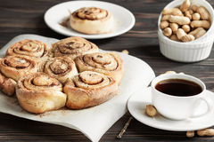 Fresh cinnamon rolls and coffee on a wooden breakfast table. Buns with cinnamon and nuts, coffee cup on a wooden background Stock Image