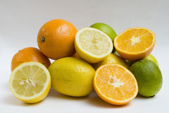 Fresh citrus fruits. A pile of whole and sliced citrus fruits including limes, oranges, and lemons.  White background Stock Photos