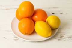 Fresh citrus fruits. Fresh oranges and lemons placed carfeully on a plate. It is a white plate and it is on a rustic white kitchen table. Both oranges and lemons royalty free stock photography