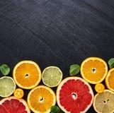 Fresh citrus fruits. On a black stone background royalty free stock image