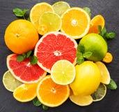 Fresh citrus fruits. On a black stone background stock image