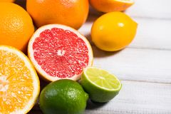 Fresh citrus fruits on a brown wooden table.  royalty free stock image