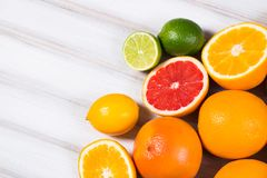 Fresh citrus fruits on a brown wooden table.  stock photo