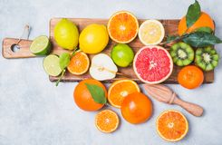 Fresh citrus fruits on cutting board. royalty free stock photography